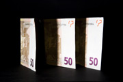 Three 50 euros notes half hidden in shadow
