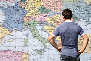 Man with hands on his hips facing a map of Europe