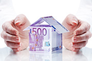 Two hands surround and protect a house made of 500 euros notes