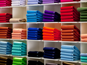 Piles of colourful tee-shirts in the stores of a shop