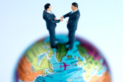 Figurine businessmen shaking hands on top of globe, close up © Stockbyte/Paul Tearle