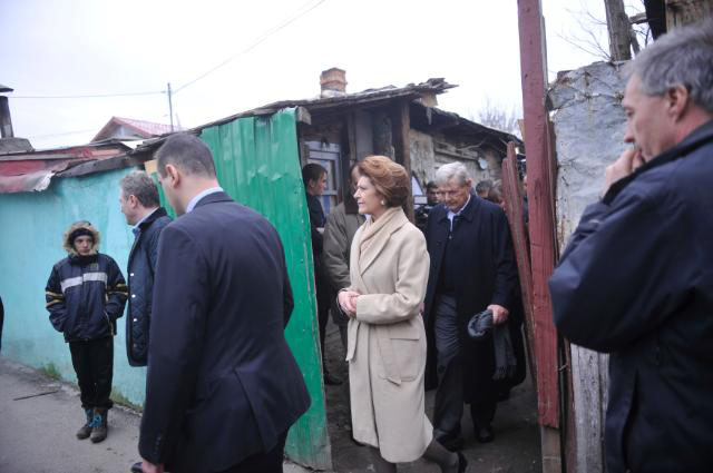 Androulla Vassiliou (c) and George Soros (2nd r) visit the Buruiana family, a Romanian Roma family at their home in Jilava