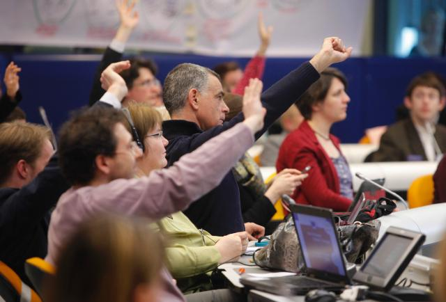 Several citizens raising their hands up during the Pan-European Citizens' Dialogue