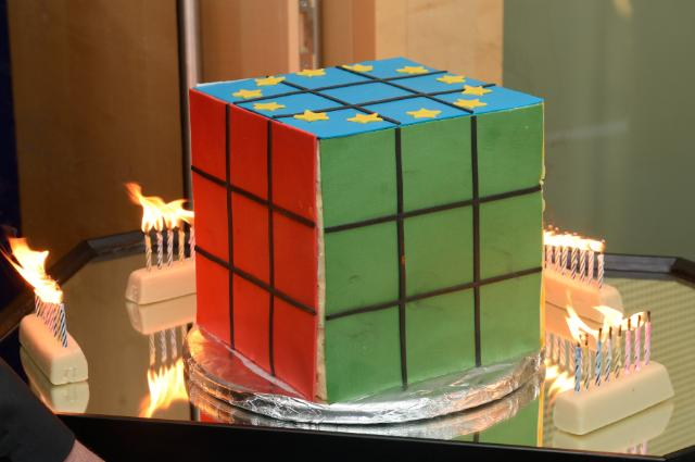 A cake in the shape of a Rubik's Cube, surrounded by inflamed candles to celebrate the 40th anniversary of this colourful device