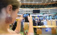 A woman taking a picture of Vytenis Andriukaitis, in the centre, with a smartphone