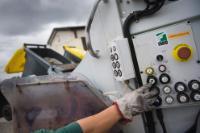 Un employé poussant le bouton du camion pour vider un container