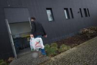 Un homme portant ses poubelles dans le local où se trouvent les containers de tri et recyclage des déchets ménager