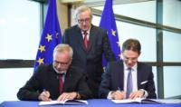 Signature of the agreement by Werner Hoyer, on the left, and Jyrki Katainen, in the presence of Jean-Claude Juncker