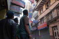 Men watching advertisement boards falling off after the earthquake of 25 April, in the neighbourhood of Tamal