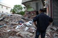 A man looking at the rubble of the city following the earthquake in the neighbourhood of Tamel