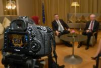A camera with its lens pointing towards Herman van Rompuy, on the right, and José Manuel Barroso, in the centre