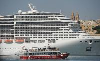 A harbour cruise boat passing a large cruise liner berthed at the Valletta waterfront
