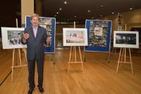 Johannes Hahn posing next to the winning photos of the competition