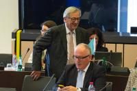 Jean-Claude Juncker, standing, and Frans Timmermans, in the foreground, using his smartphone