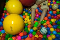 A child playing with mutli-coloured balls