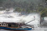 Residents (on the right) standing along a sea wall as high waves pounded them amidst strong winds as Typhoon Haiyan hit the city of Legazpi, Albay province, south of Manila