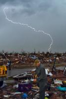 Lightning during a storm, while survivors of the tornado Moore, Oklahoma, roam the rubble