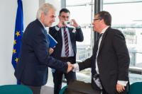 Handshake between Franck Proust, on the right, and Christos Stylianides