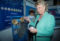 Viviane Reding, next to a distributor of false coins com...