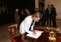 Federica Mogherini, in the foreground, signing the guest book
