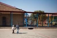 Two children holding hands in the yard of the primary school Khangezile