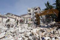 Rescuers search in the remains of a building which collapsed the day before during a violent earthquake  in the Abruzzo capital L'Aquila