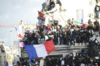 Several participants in the cortege on the monument of the statue of Marianne, with the French flag floating in the foreground