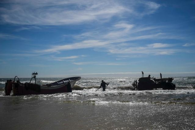 Fishing boat pulled to the sea with the help of the fishermen and a tractor
