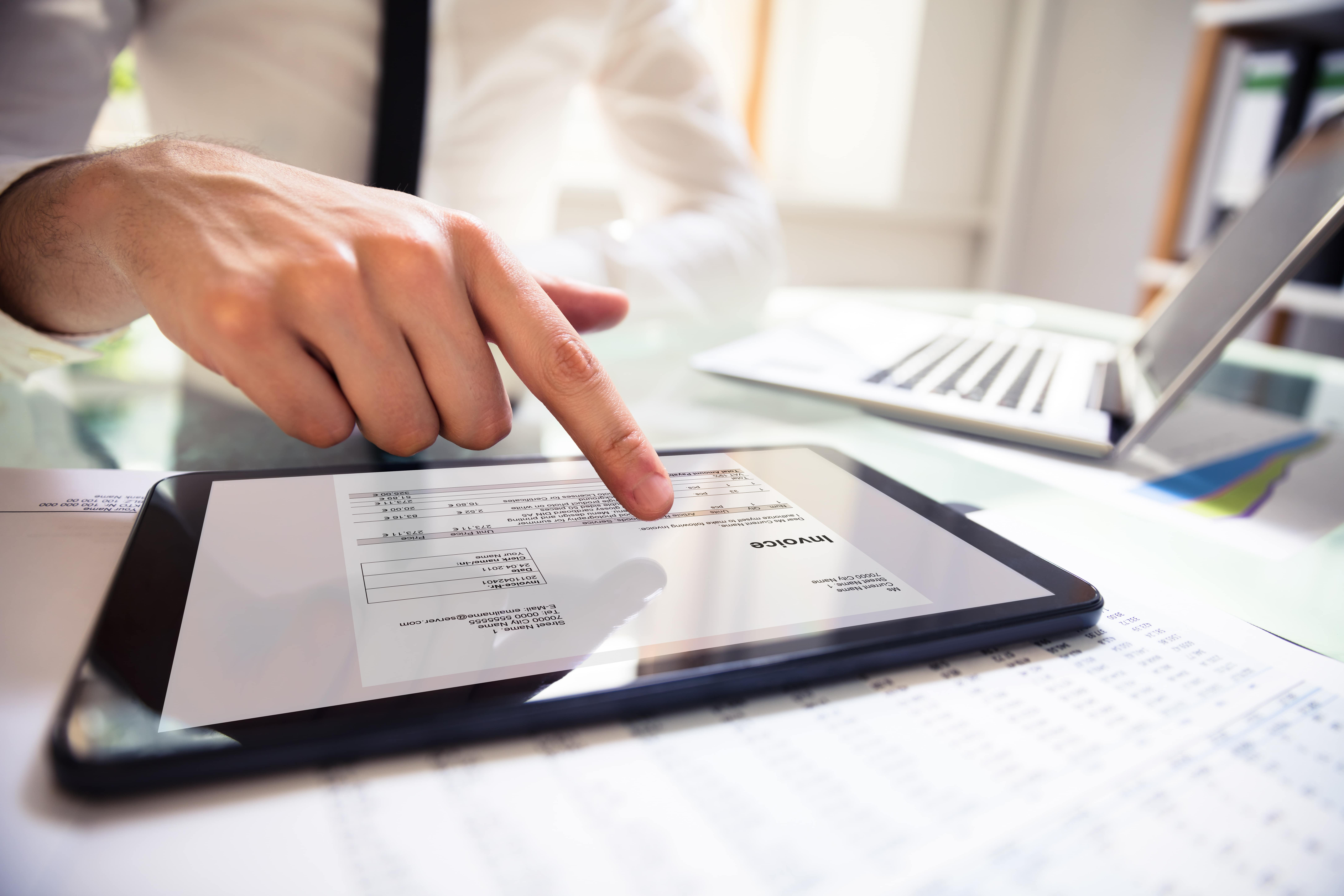 A businessman looking at an electronic invoice on his tablet at a wooden desk with a tablet and computer on it, his face is not visible