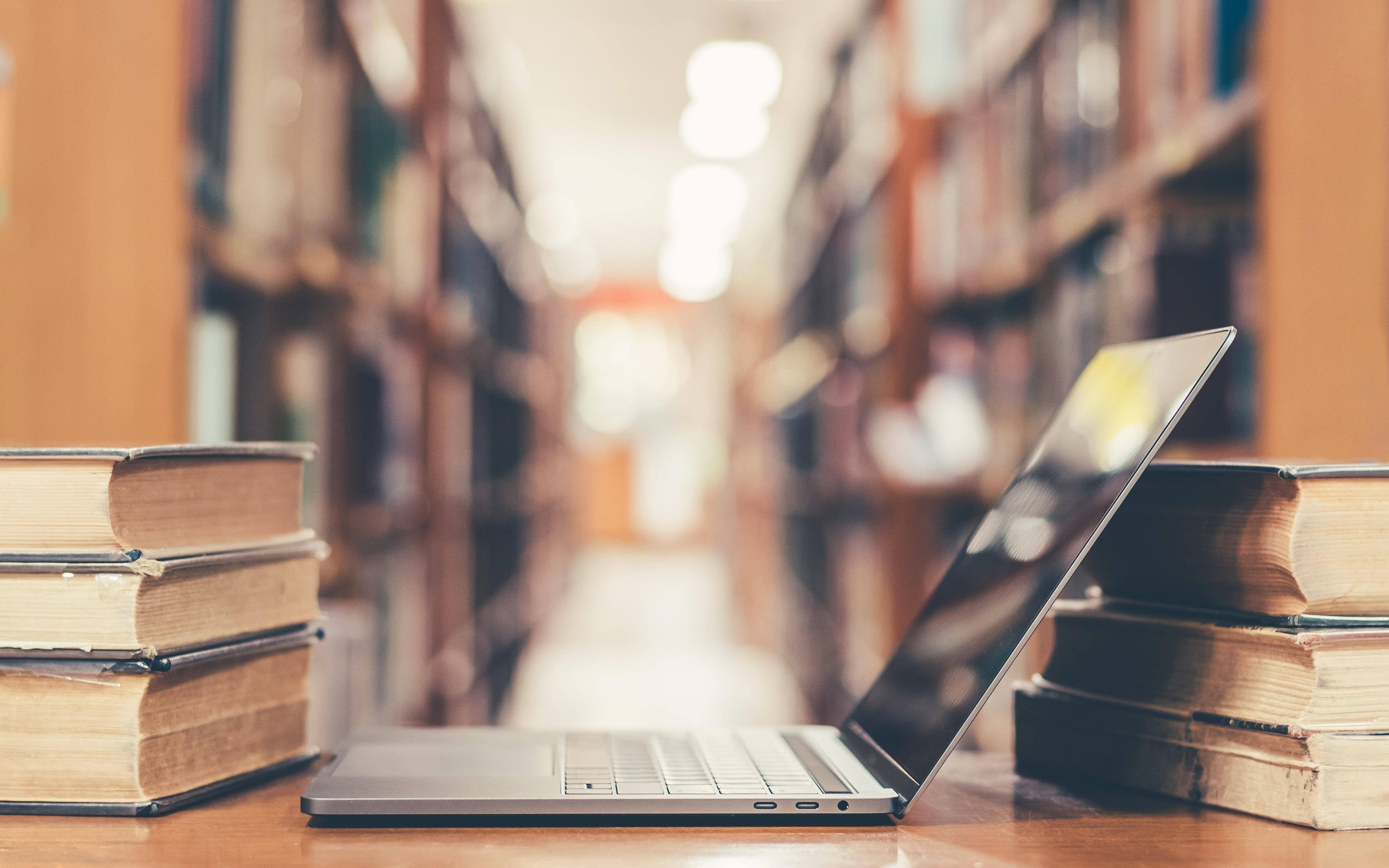 laptop on a desk flanked by book stacks