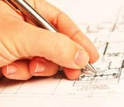 Hand holding pen over technical drawing