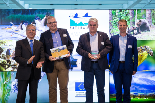 European Commissioner for Environment, Maritime Affairs and Fisheries, Karmenu Vella and Ignace Schops, president of EUROPARC Federation and jury member with Vaios Koutis and Periklis Tzovlas, Callisto – winners of the 2018 Reconciling interests / perception Award