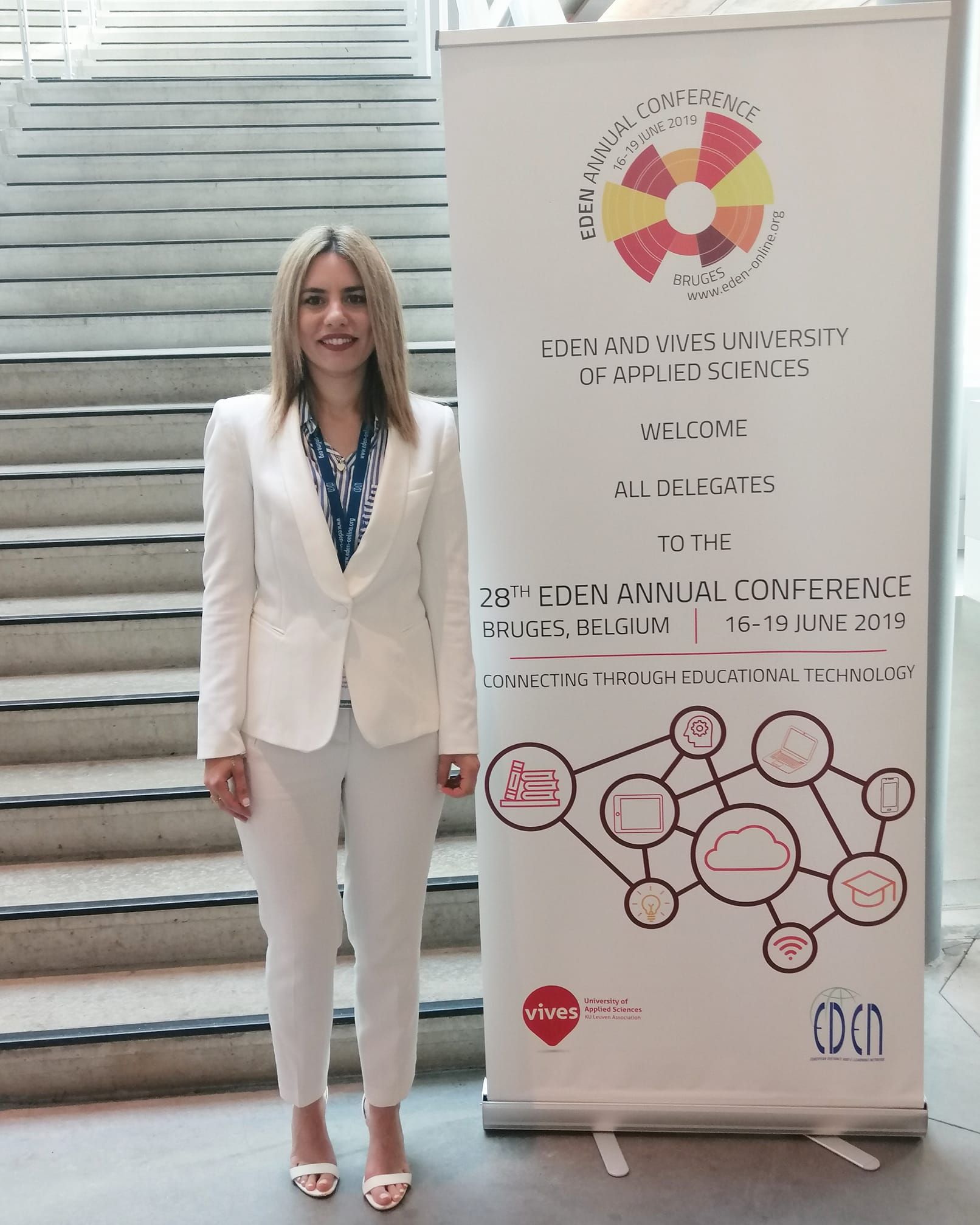 Angeliki standing next to the rollup of the EDEN conference