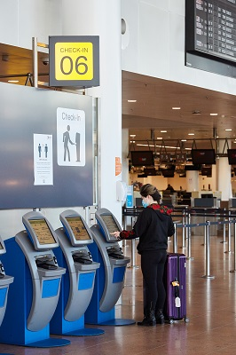 Woman operating her check-in at an automatic machine, airport