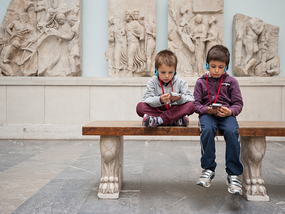 Two children seating in a museum