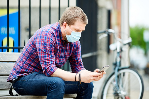 man with mask checking his phone