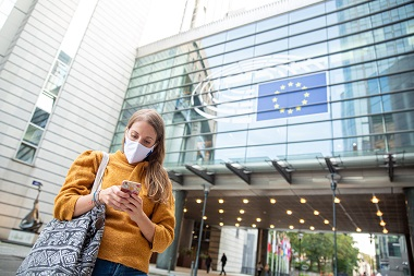 woman in front of EU commission building looking at her smartphone