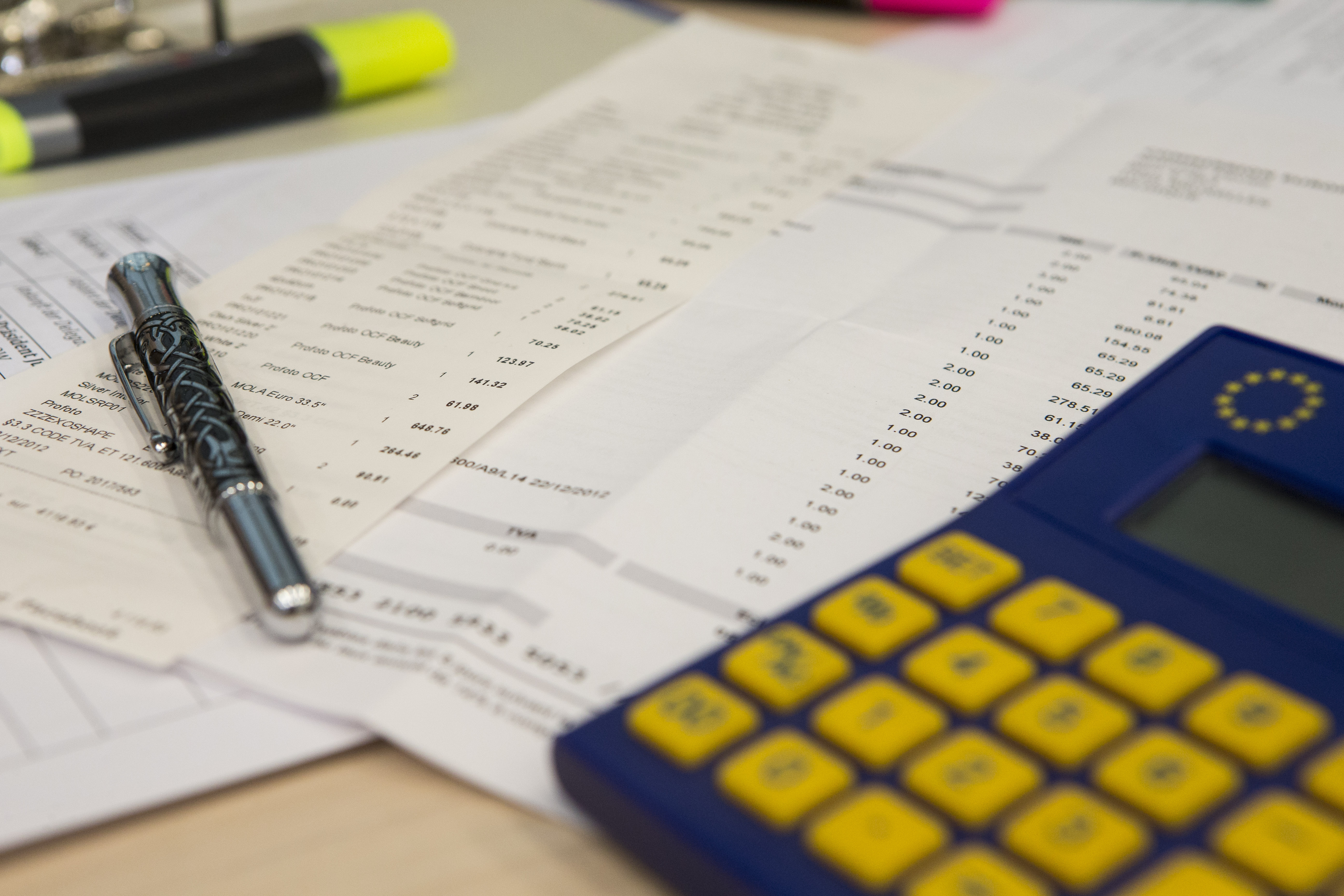 A pen and a calculator lie on top of a financial report