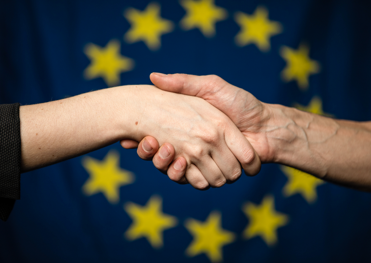 A handshake in front of the European flag