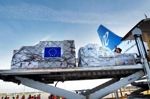 Cargo freight on palettes branded with EU flag being loaded onto an airplane.
