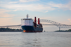 A wide river with a ship approaching a large bridge