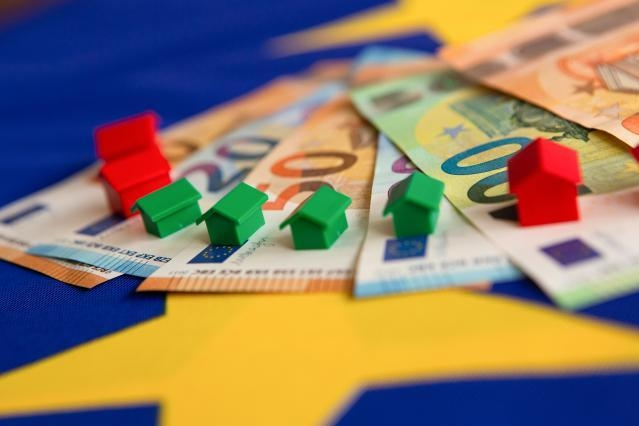 Little model houses on top of Euro notes spread out on a surface