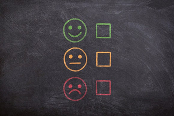 Blackboard with three drewn faces, one smiling, on neutral, and on unhappy, with a square box to tick next to them