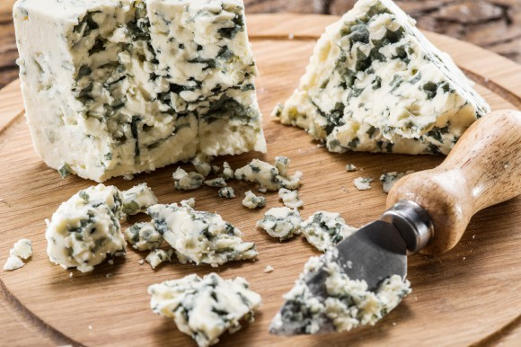 Danish blue cheese and a knife on a cutting board, cheese already cut into smaller pieces with the knife