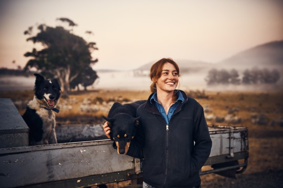Young female farmer petting dog on trailer of a pick-up truck standing in a field