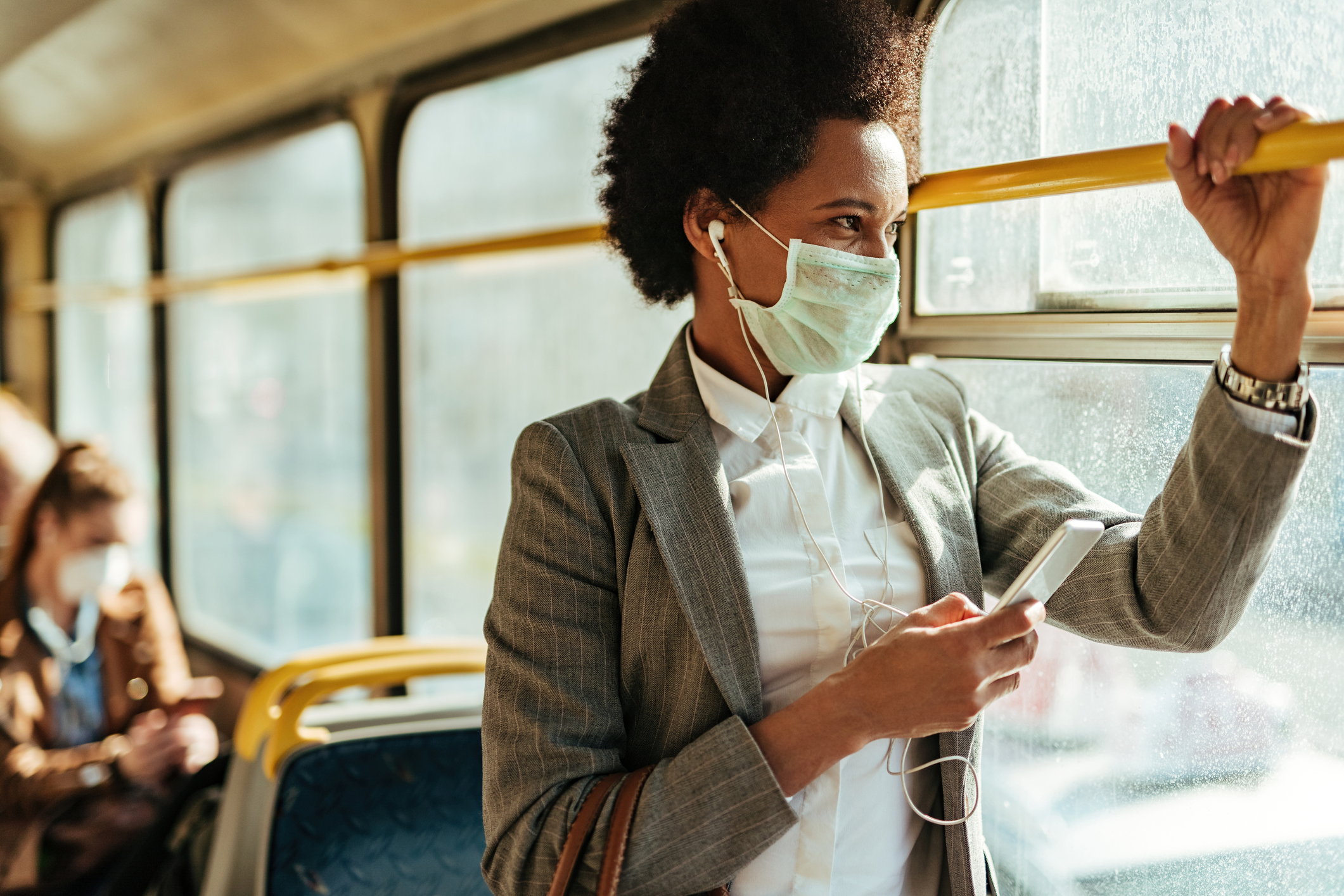 picture of business woman with mask on a bus