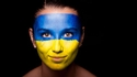 A women with the colours of the Ukrainian flag painted on her face