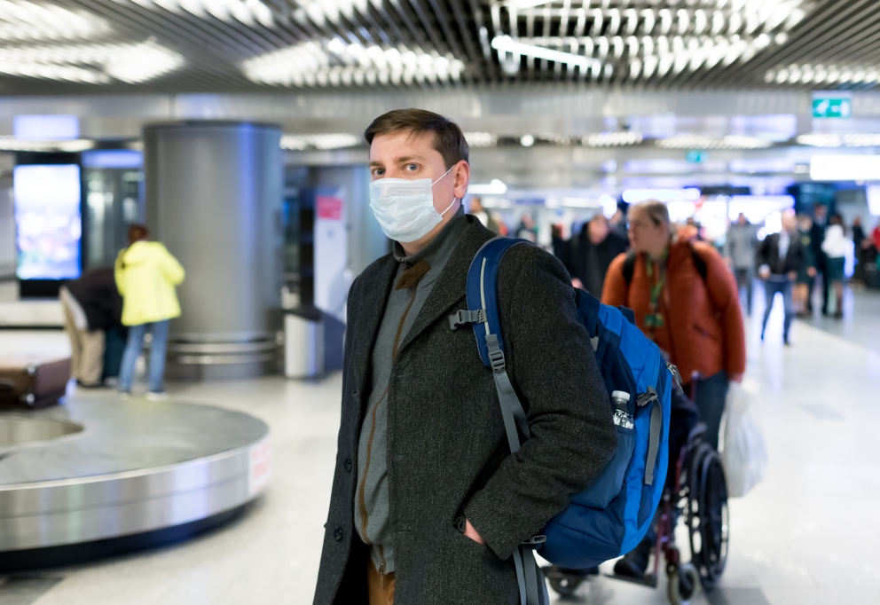 photo of a person with mouthmask waiting at an airport luggage belt