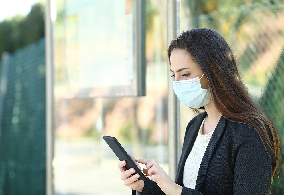 photo of a young woman with a mouthmask checking her smartphone