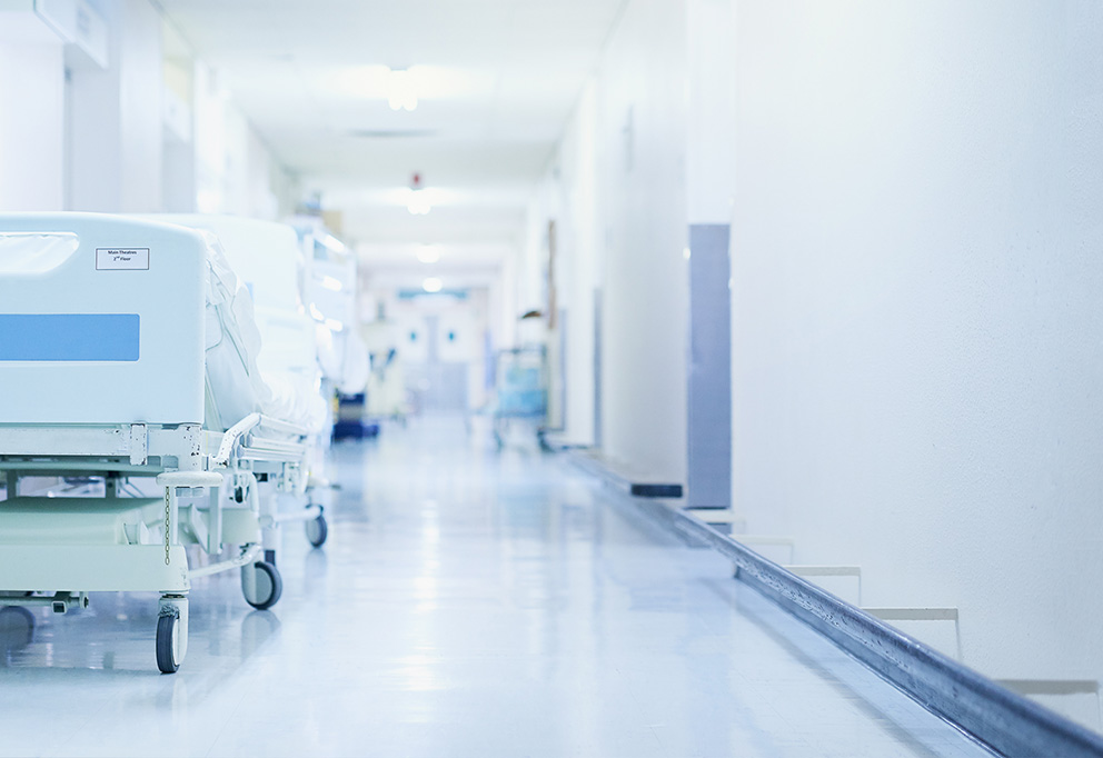 photo of a hospital corridor with a hospital bed in the front